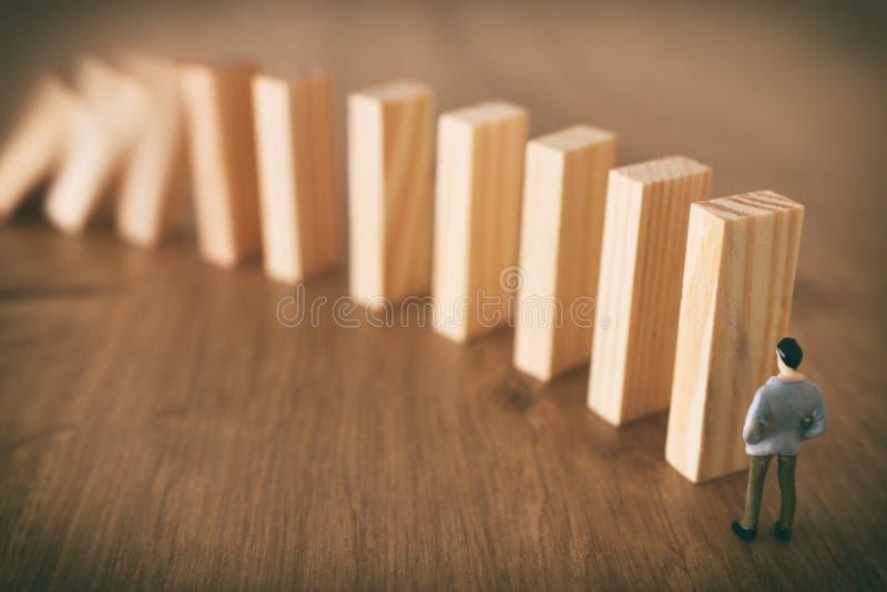Aff?r En man står framme av dominobrickor och ordnar dem men är omedveten av faran av deras nedgång riskkontroll och royaltyfria bilder