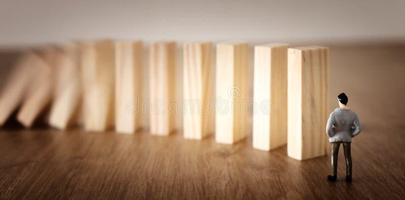 Aff?r En man står framme av dominobrickor och ordnar dem men är omedveten av faran av deras nedgång riskkontroll och royaltyfri foto
