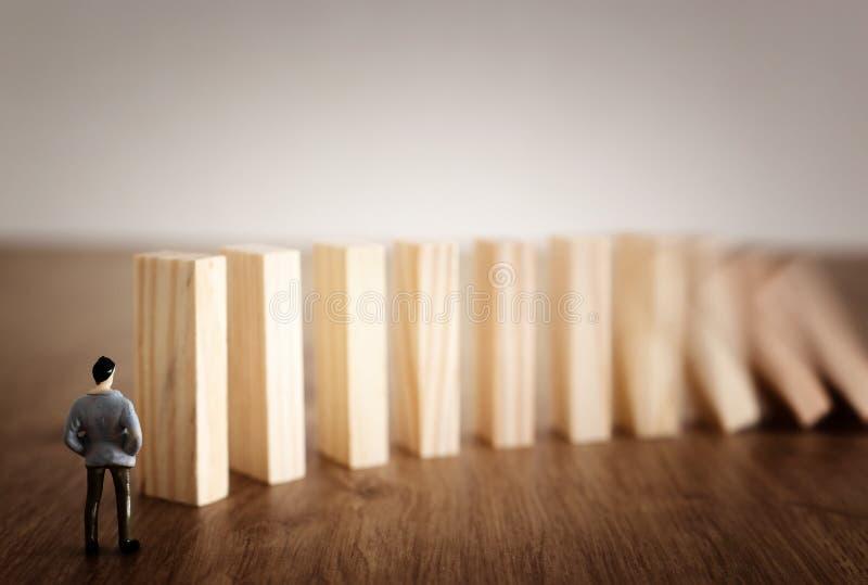 Aff?r En man står framme av dominobrickor och ordnar dem men är omedveten av faran av deras nedgång riskkontroll och royaltyfri fotografi