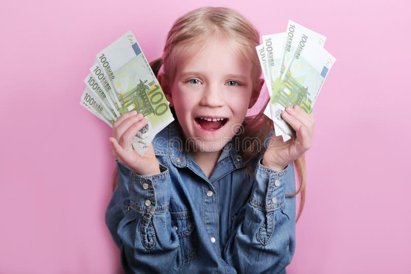 Aff?r och pengarbegrepp - lycklig liten flicka med eurokassapengar ?ver rosa bakgrund arkivfoto