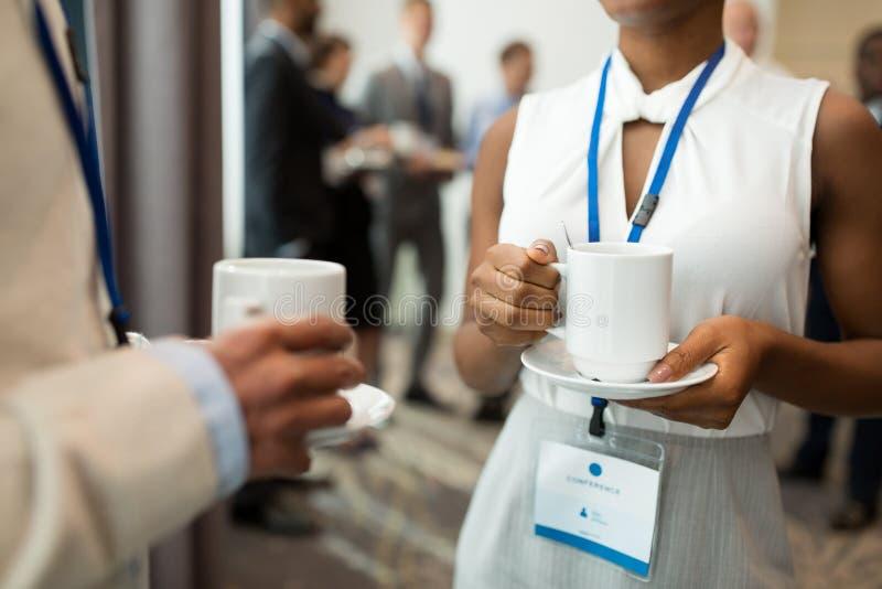 Aff?rsfolk med konferensemblem och kaffe arkivfoton