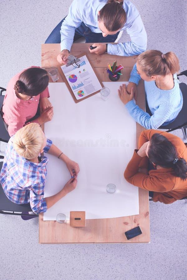 Aff?rsfolk som sitter och diskuterar p? m?tet, i regeringsst?llning arkivfoto