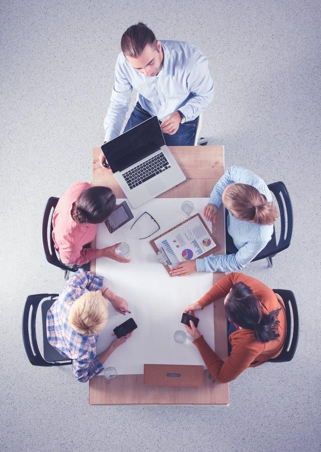 Aff?rsfolk som sitter och diskuterar p? aff?rsm?tet, i regeringsst?llning royaltyfri bild