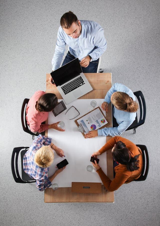 Aff?rsfolk som sitter och diskuterar p? aff?rsm?tet, i regeringsst?llning arkivfoton