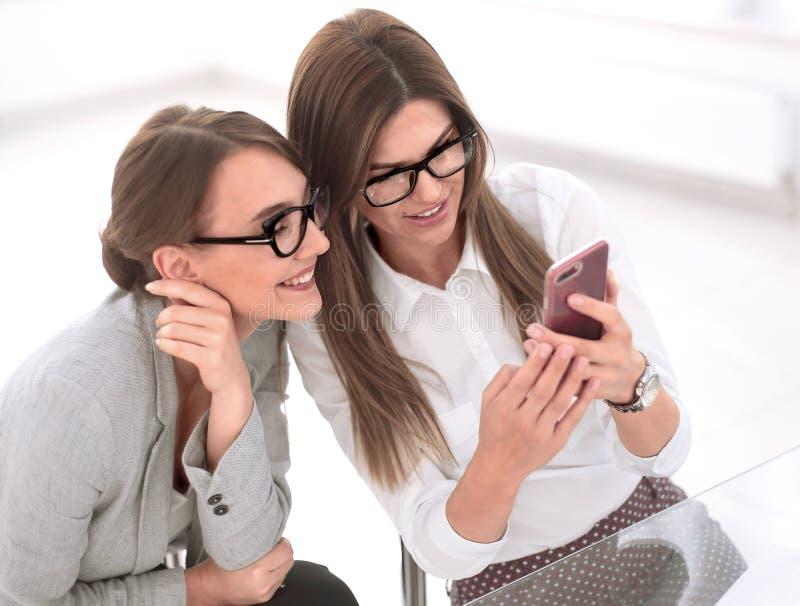 Aff?rskollegor tar selfies som sitter p? skrivbordet royaltyfri fotografi