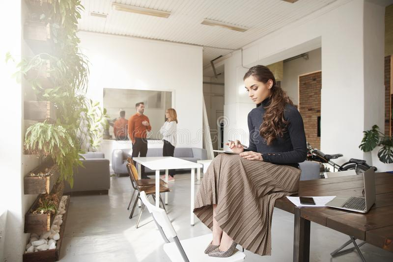 Aff?rskvinna som anv?nder hennes digitala minnestavla, medan sitta i kontoret och arbeta royaltyfri bild