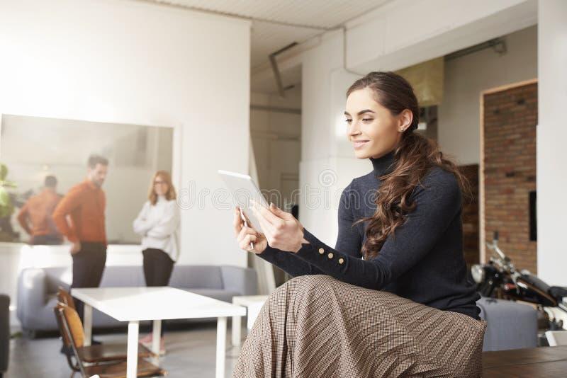 Aff?rskvinna som anv?nder hennes digitala minnestavla, medan sitta i kontoret och arbeta royaltyfria foton
