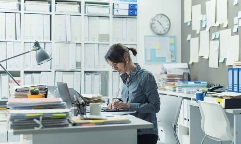 Aff?rskvinna som fungerar i kontoret fotografering för bildbyråer