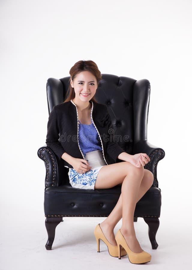Aff?rskvinna som kopplar av i en stol royaltyfri bild