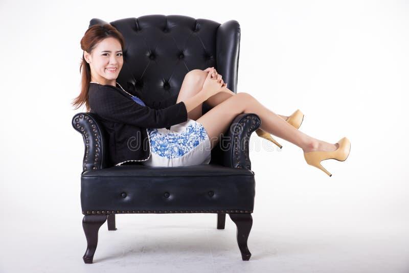 Aff?rskvinna som kopplar av i en stol arkivfoton