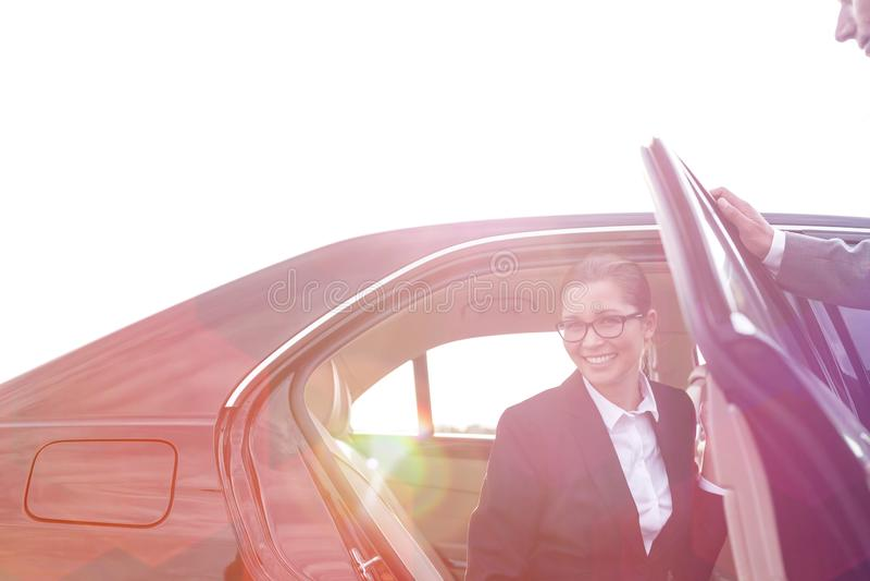 Aff?rskvinna som lands?tter fr?n bilen av kollegan mot himmel royaltyfria foton