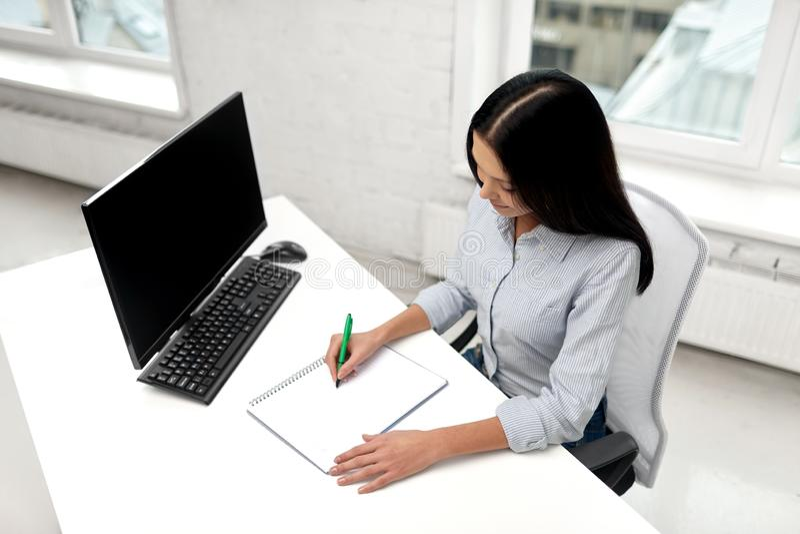 Aff?rskvinna som skriver till anteckningsboken p? kontoret royaltyfri foto