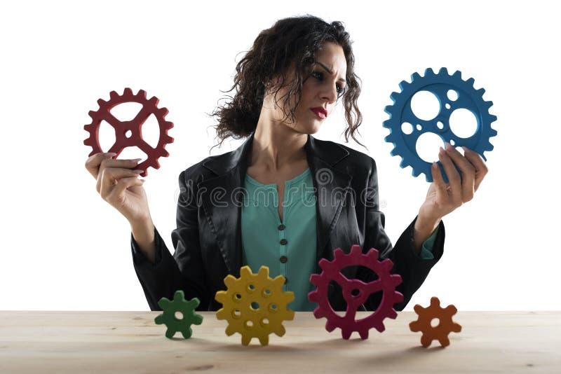 Aff?rskvinnan f?rs?ker att arbeta med kugghjul Begrepp av teamwork och partnerskap bakgrund isolerad white arkivfoto