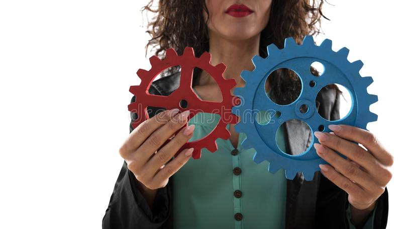 Aff?rskvinnan f?rs?ker att f?rbinda kugghjulstycken Begrepp av teamwork, partnerskap och integration arkivfoton