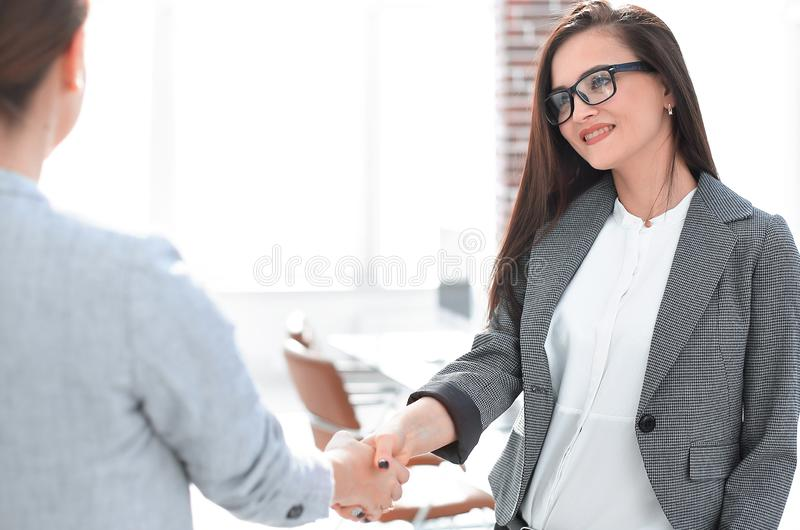 Aff?rskvinnan m?ter klienten med en handskakning royaltyfria foton