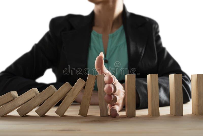 Aff?rskvinnan stoppar en kedjenedg?ng som dominobrickaleken Begrepp av att f?rhindra kris och fel i aff?r royaltyfria bilder