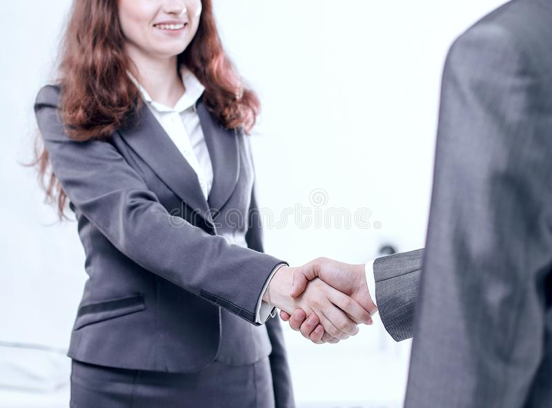 Aff?rskvinnan v?lkomnar aff?rspartnerns handskakning royaltyfri bild