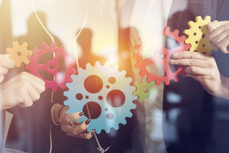 Aff?rslaget f?rbinder stycken av kugghjul Teamwork-, partnerskap- och integrationsbegrepp dubbel exponering arkivfoto