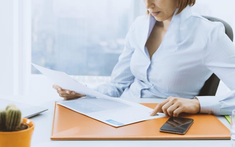Aff?rsledare som kontrollerar finansiella rapporter i kontoret arkivfoton