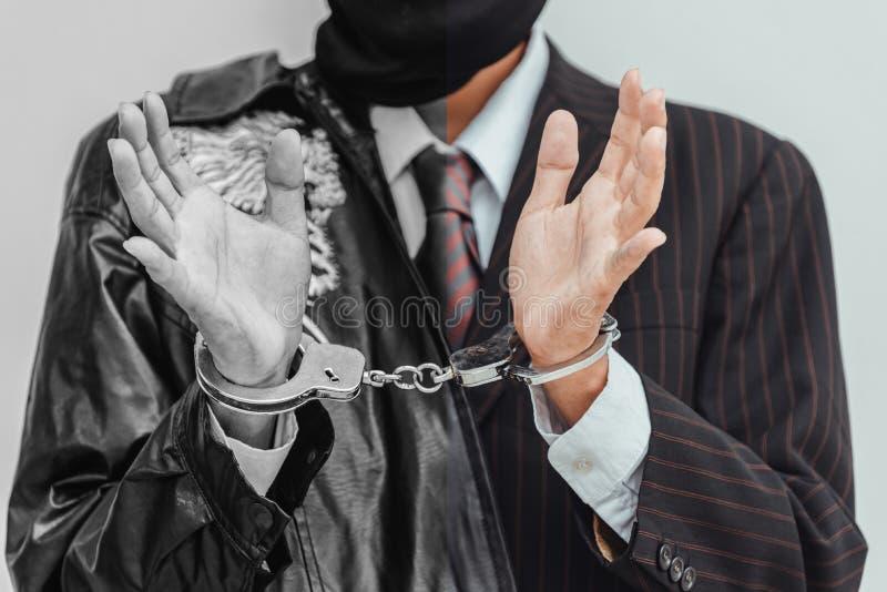Aff?rsm?n arresterades och handf?ngslades, d?rf?r att g?r den olagliga aff?ren, med svart bakgrund till den m?rka aff?rsid?en royaltyfri bild
