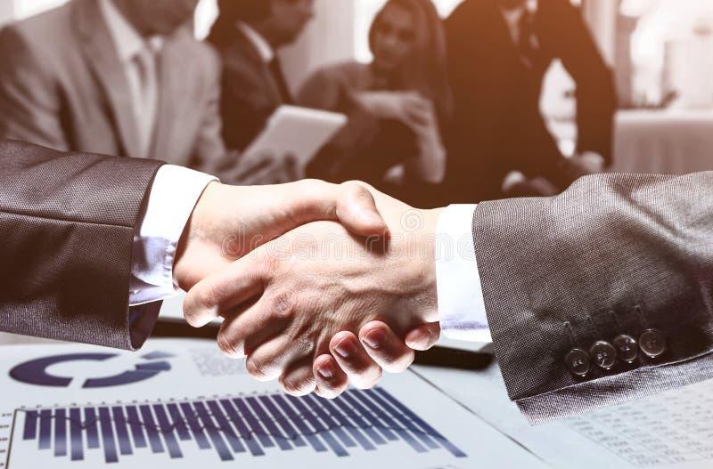 Aff?rsman En hand f?r handskakning G?r avtalet Arbetsaff?rslag i bakgrunden fotografering för bildbyråer
