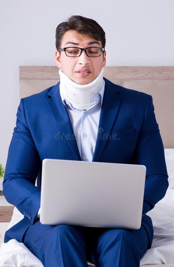 Aff?rsman med halsskadan som hemifr?n arbetar royaltyfri foto