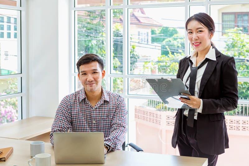 Aff?rsman och sekreterare Yrkesmässiga asiatiska businesspeople som arbetar på datoren arkivfoto