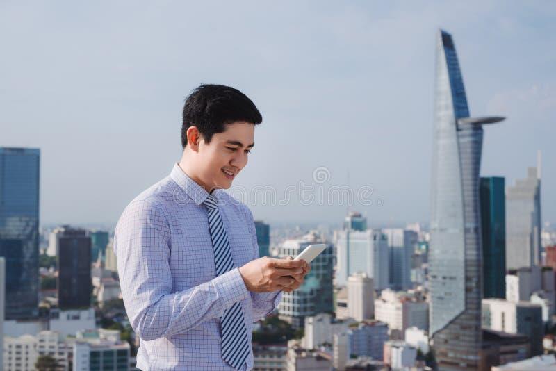 Aff?rsman som anv?nder mobiltelefonen app som f?rutom smsar kontoret i stads- stad med skyskrapabyggnader i bakgrunden royaltyfria bilder