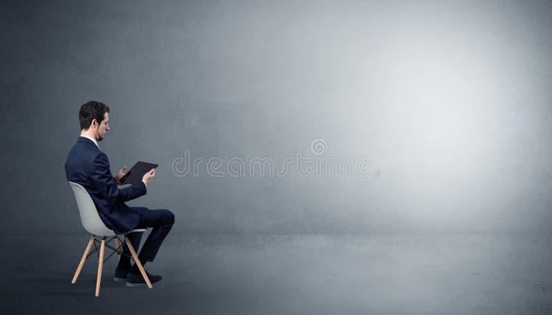 Aff?rsman som blir i ett tomt rum med material p? hans varv royaltyfria foton