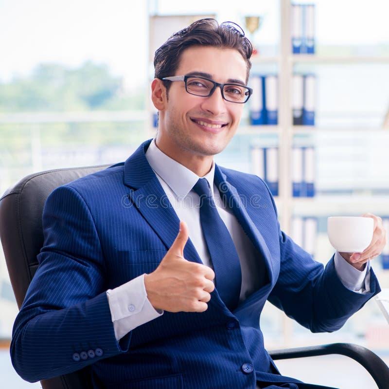 Aff?rsman som dricker kaffe i kontoret under avbrott arkivbilder