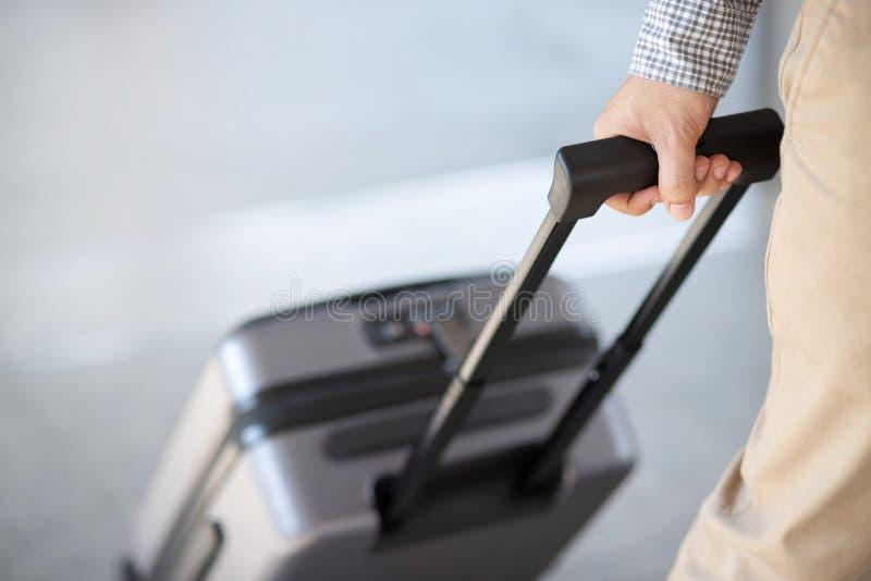 Aff?rsman som g?r yttersidakollektivtrafikbyggnad med bagage i rusningstid Affärsresande som drar resväskan i modern airp fotografering för bildbyråer