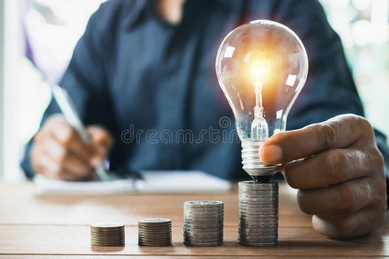 Aff?rsman som i regeringsst?llning rymmer den ljusa kulan p? skrivbordet och skriver p? anm?rkningsboken den f?r finansiellt och  arkivfoton