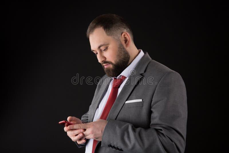 Aff?rsmannen ansade v?l manh?llsmartphonen F?r dr?ktbruk f?r man sociala n?tverk f?r formell smartphone Grabb som surfar internet arkivbild