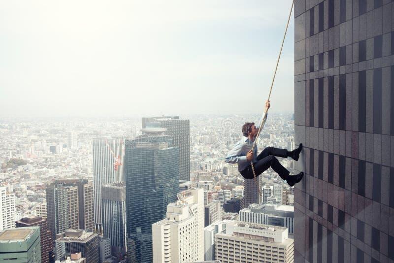 Aff?rsmannen kl?ttrar en byggnad med ett rep Begrepp av beslutsamhet royaltyfri bild
