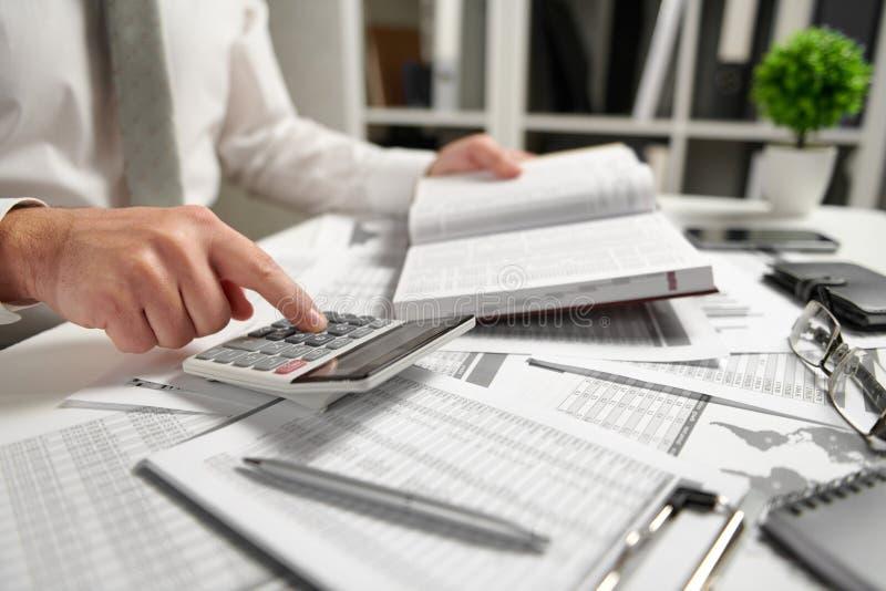 Aff?rsmannen som arbetar p? kontoret och ber?knar finans, l?ser och skriver rapporter begrepp f?r finansiell redovisning f?r aff? arkivbilder