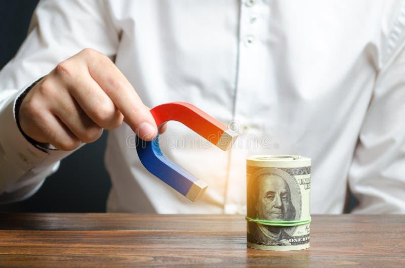 Aff?rsmannen tilldrar pengar med en magnet Tilldragning av pengar och av investeringar för affärsavsikter och starter ?ka vinster royaltyfria bilder