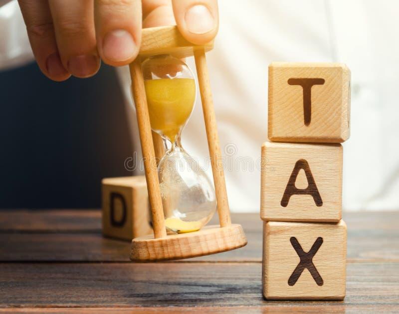 Aff?rsmans hand som rymmer ett timglas n?ra tr?kvarteren med ordskatten pay beskattar tid till Begreppet av den ?rliga taxatioen arkivfoto