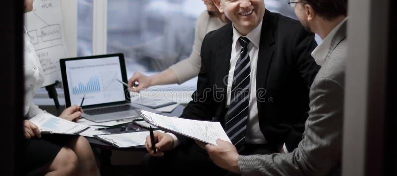 Aff?rspartners som kopplas in i dialog i ett modernt kontor royaltyfri foto