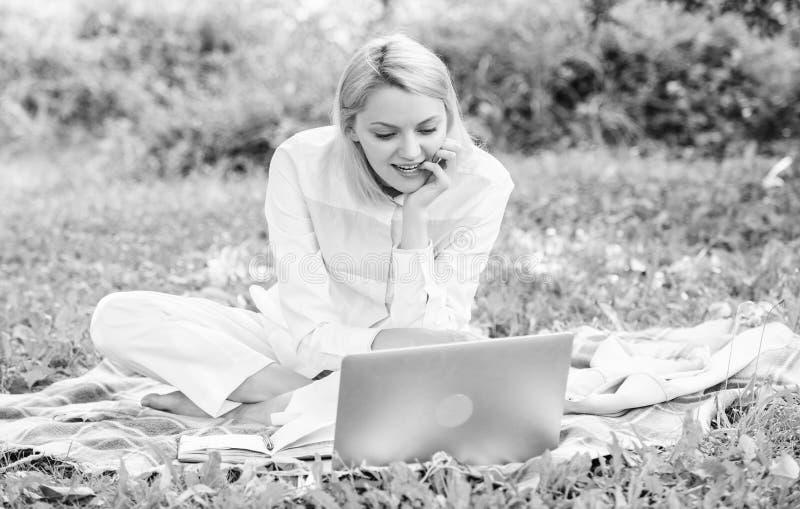 Aff?rspicknickbegrepp Moment som ska startas frilansa aff?r Kvinnan med b?rbara datorn eller anteckningsboken sitter p? filtgr?sp arkivfoto