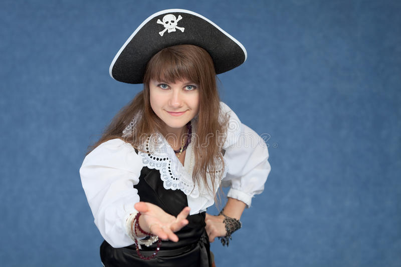 Affable girl in suit of the sea medieval pirate. The affable girl in a suit of the sea medieval pirate on blue background royalty free stock photo