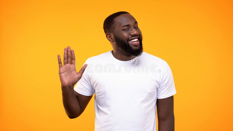 Affable young black man showing palm, waving hand neighborly yellow background stock photos