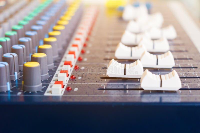 Affaiblisseur haut étroit du vieux volume de mixeur son ajustant le contrôleur de boutons dans des baisses de salle de commande e photographie stock libre de droits