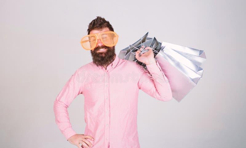 Affaire profitable Consommateur d?pendant de achat Concept total de vente Hippie barbu d'homme avec des sacs ? provisions de sort images stock