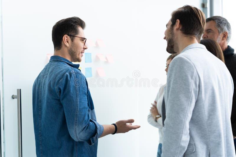 Affaires, éducation et concept de bureau - équipe d'affaires avec le conseil de secousse dans le bureau discutant quelque chose images stock