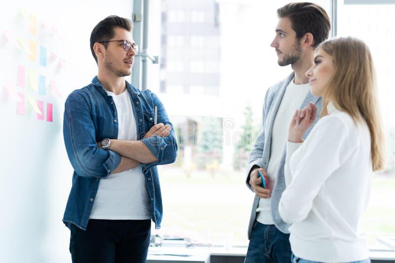Affaires, éducation et concept de bureau - équipe d'affaires avec le conseil de secousse dans le bureau discutant quelque chose photos stock