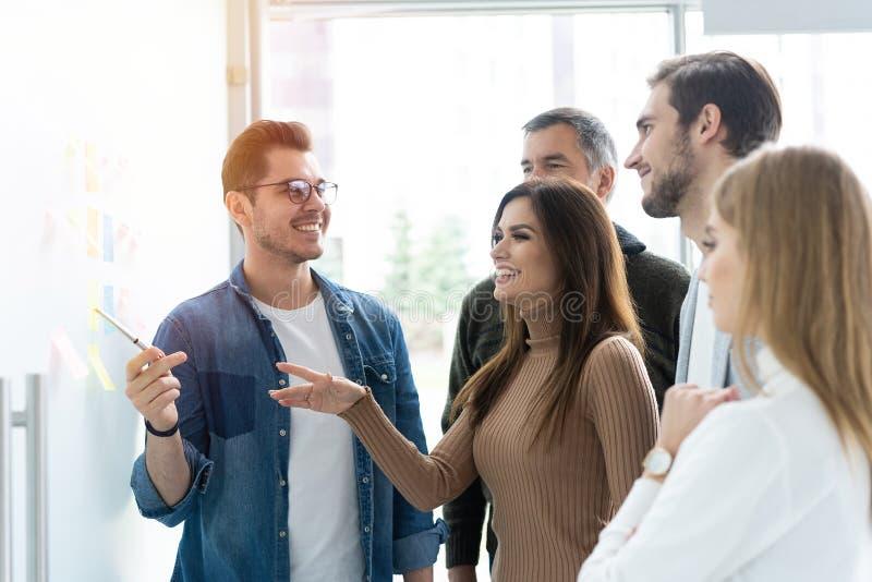 Affaires, éducation et concept de bureau - équipe d'affaires avec le conseil de secousse dans le bureau discutant quelque chose photo libre de droits