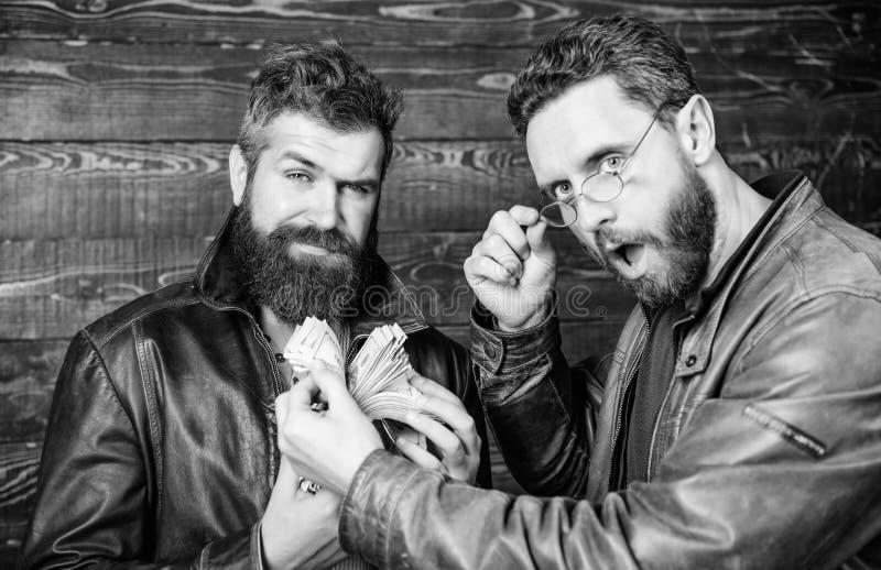 Affaires de Mafia Bénéfice impressionnant Hippie barbu brutal d'hommes utiliser la veste en cuir et tenir l'argent d'argent liqui image libre de droits