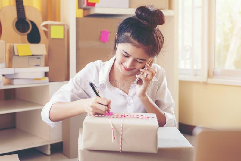 Affaires de sourire asiatiques de propriétaire de jeunes femmes appelle la commande reçue du client en ligne et emballant le prod photographie stock