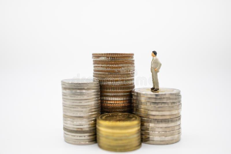 Affaires, finances, économie et concept sûr Fermez-vous des chiffres miniatures d'homme d'affaires se tenant sur la pile de pièce photo stock