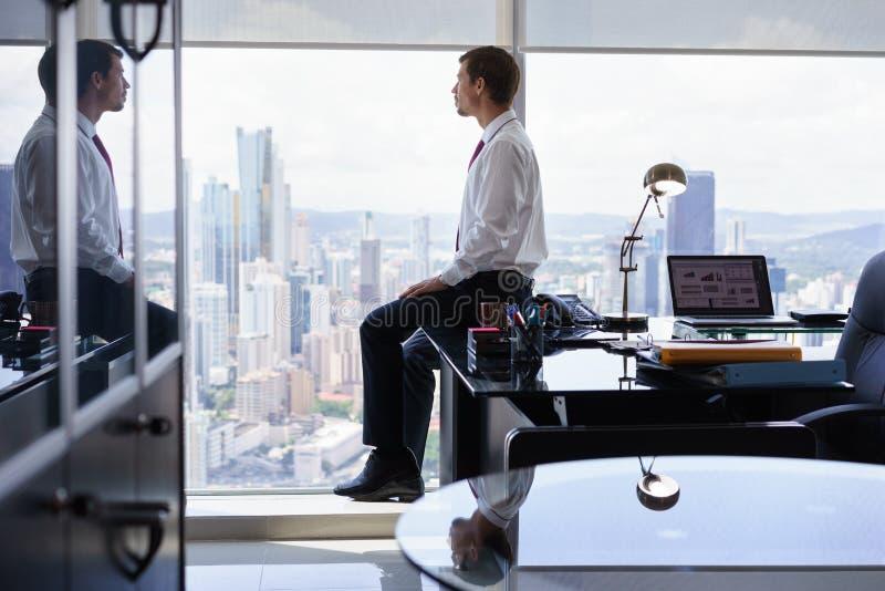 Affaires Person Sits On Desk Looking hors de fenêtre de bureau photo libre de droits